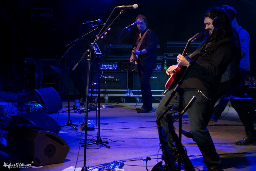 Dan Tracey (back of shot) watches on from the right side of the stage as Alastair Greene tackles a solo for the Alan Parsons Live Project.